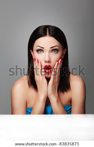 Portrait of young surprised woman holding her face - stock photo