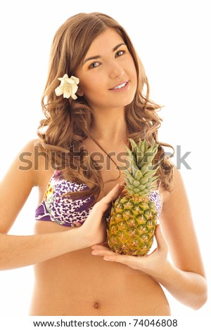 Portrait of young tanned pretty brunette woman with flower in her hair holding fresh pineapple in her hand wearing swimsuit