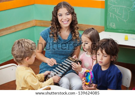 Portrait of young teacher playing xylophone with students in preschool - stock photo