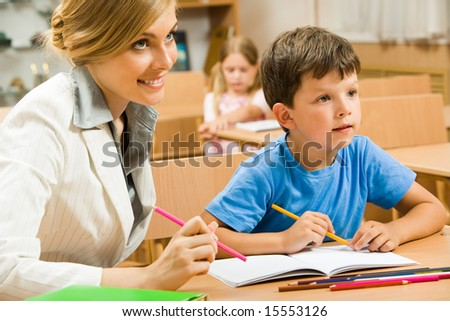 Portrait of young teacher sitting by one of pupils while both looking at something interesting
