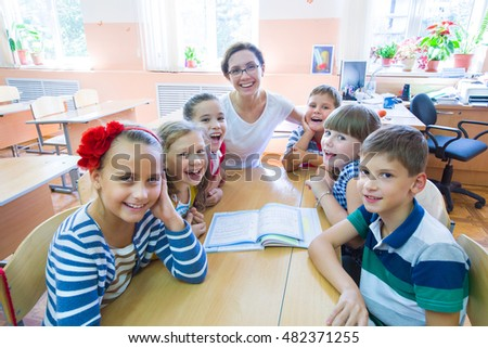 portrait of young teacher with children in elementary school