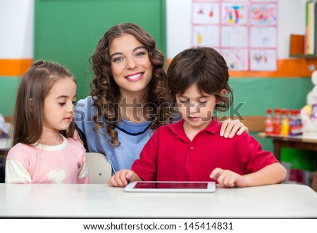 Portrait of young teacher with children using digital tablet at classroom desk - stock photo