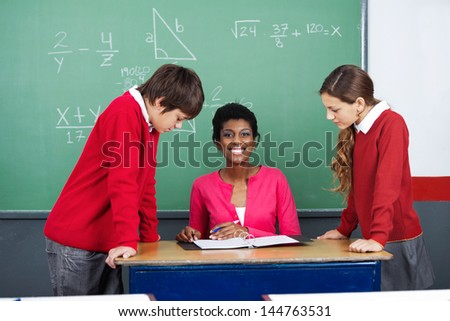Portrait of young teacher with students standing at desk in classroom