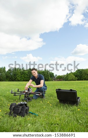 Portrait of young technician assembling UAV helicopter in park against cloudy sky - stock photo