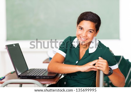 portrait of young teen school girl sitting in class with laptop - stock photo
