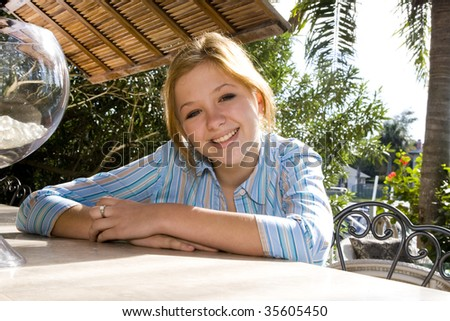 Portrait of young teenage girl leaning on table outdoors - stock photo