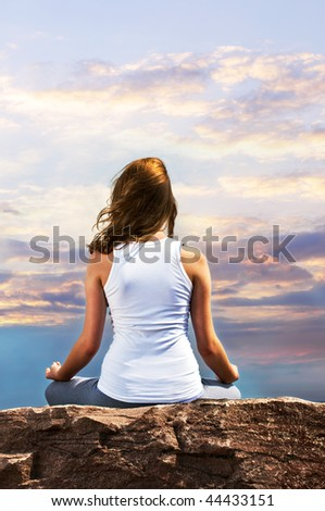 Portrait of young teenage girl practicing yoga at sunset - stock photo