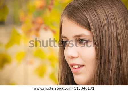 Portrait of young teenage girl with blurred yellow autumn leaves in the background - copy space on the yellow leaves - stock photo