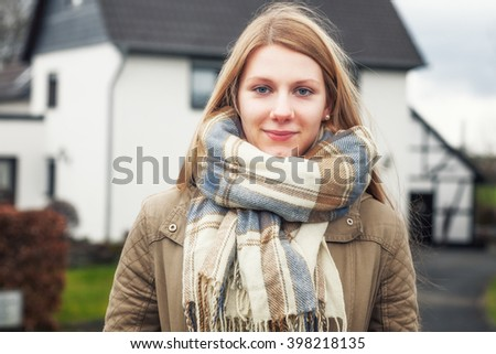 Portrait of young teenage girl with long blond hair outside house - stock photo