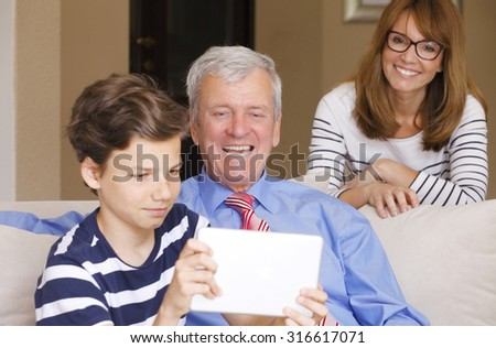 Portrait of young teenager boy with digital tablet sitting at sofa with his mother and grandfather while taking self portrait with touchpad.