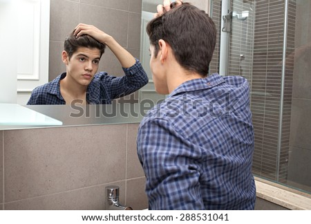 Portrait of young teenager man looking at himself in a home bathroom mirror doing his hair and getting ready in the morning, home interior. Health and well being, male care and grooming, indoors. - stock photo