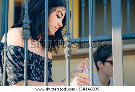 Portrait of young thoughtful woman with a lemonade glass in her hands sitting outdoors on the home stairs. Young people problems concept. - stock photo