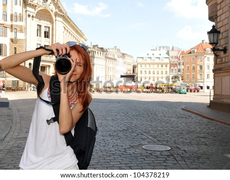 Portrait of young tourist with camera - stock photo