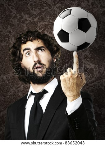 portrait of young trainer playing with a soccer ball - stock photo