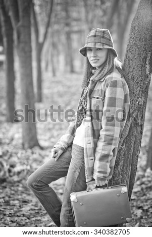 Portrait of young traveler in autumn landscape. black and white image - stock photo