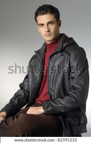 Portrait of young trendy male model on light background - stock photo