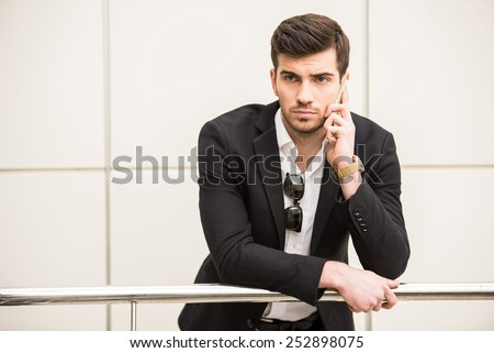 Portrait of young trendy man is talking by phone. - stock photo