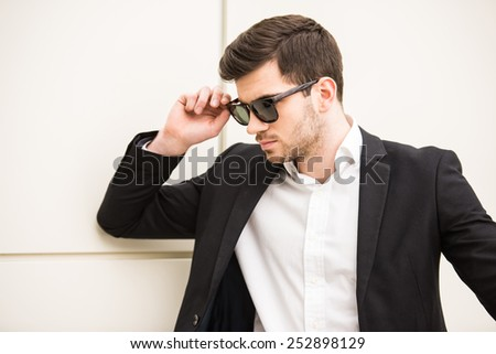 Portrait of young trendy man with black glasses is posing in front of a wall. - stock photo
