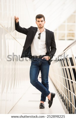 Portrait of young trendy man with is posing in modern office. - stock photo