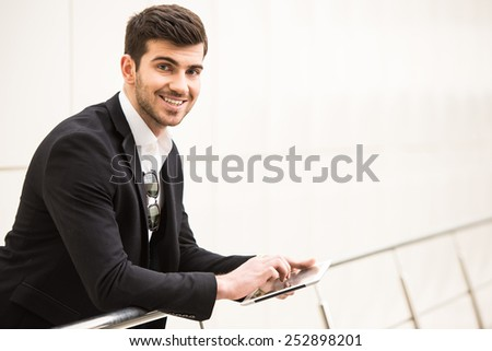 Portrait of young trendy man with tablet is posing in front of a wall. - stock photo
