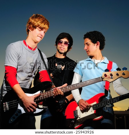 Portrait of young trendy musicians playing electric guitars - stock photo