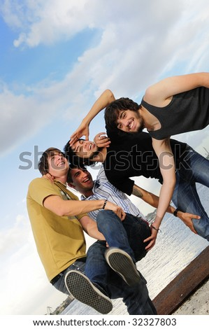 Portrait of young trendy team of male friends having fun outdoors - stock photo