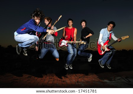 Portrait of young trendy teenager group jumping with musical instruments - stock photo