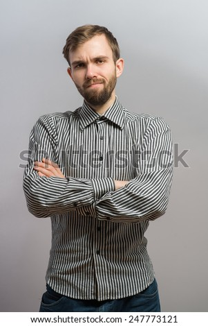 Portrait of young unhappy man posing against grey background. Handsome young hispanic male model standing with his arms crossed looking at camera. - stock photo