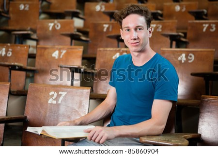 Portrait of young university student sitting in lecture hall - stock photo