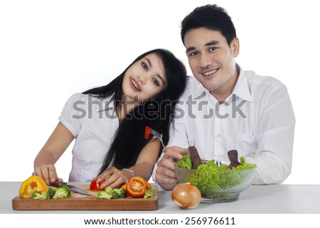 Portrait of young vegetarian couple with fresh salad, smiling at the camera isolated on white