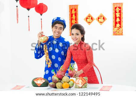 Portrait of young Vietnamese couple at festive table in their house decorated for Tet - stock photo