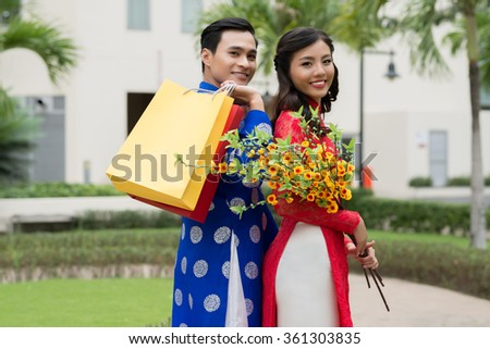 Portrait of young Vietnamese family in traditional costumes going to Tet celebration - stock photo