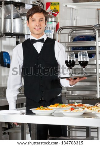 Portrait of young waiter holding wineglasses in tray with pasta dishes on commercial kitchen counter