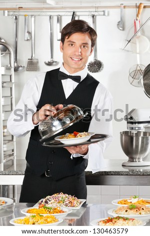 Portrait of young waiter lifting the cover of cloche at commercial kitchen - stock photo