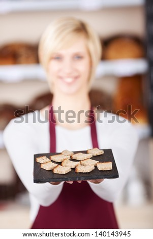 Portrait of young waitress holding bread tray in cafe
