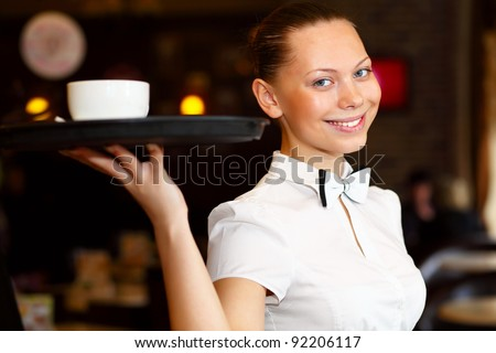 Portrait of young waitress in white blouse holding a tray - stock photo