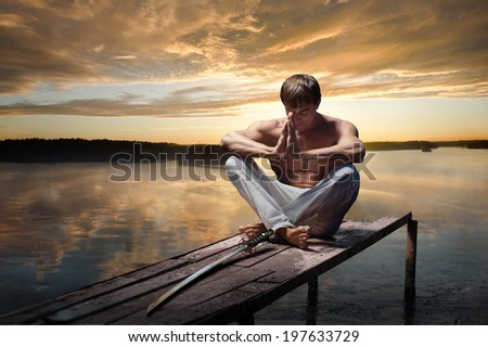 Portrait of young warrior with Japanese sword on sunset background - stock photo