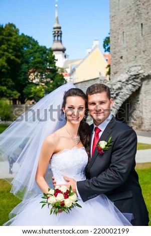portrait of young wedding couple near church, beautiful bride with groom , summer nature outdoor - stock photo