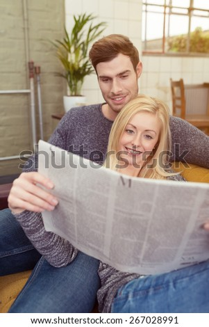 Portrait of Young White Couple Resting at the Sofa in Living Room While Reading Newspaper - stock photo