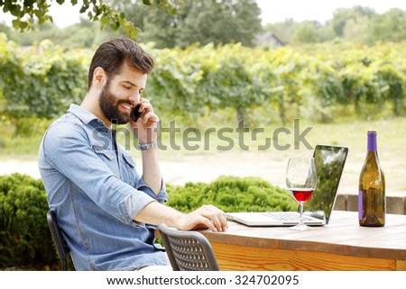 Portrait of young wine estate owner sitting at his wine cellar and making call while working online.  - stock photo