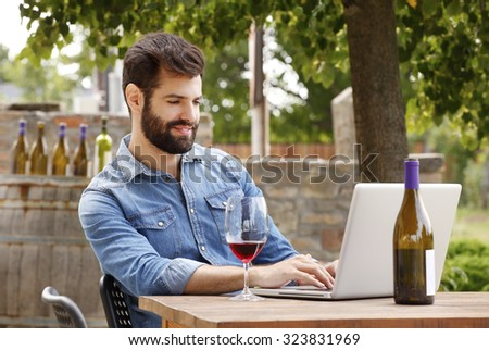 Portrait of young winemaker sitting at wine cellar in front of his laptop and working while tasting red wine. Small business.  - stock photo