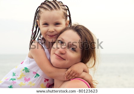 Portrait of young woman and her daughter on a beach - stock photo