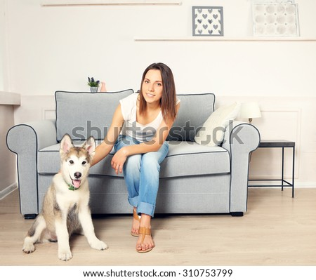 Portrait of young woman and her malamute dog in room - stock photo