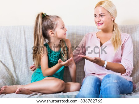 Portrait of young woman and little girl having funny conversation - stock photo