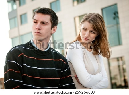 Portrait of young woman and man outdoor on street having relationship problems - stock photo