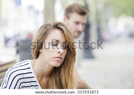 Portrait of young woman and man outdoor on street having relationship problems