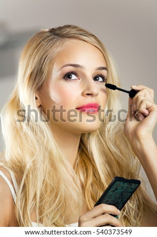 Portrait of young woman applying mascara at home. Beauty and make up concept.