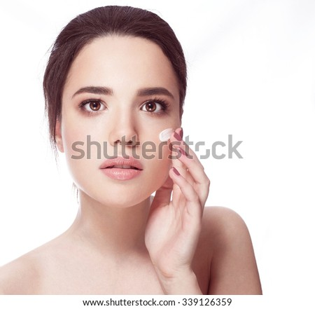 Portrait of young woman applying moisturizer cream on her pretty face - white background - stock photo