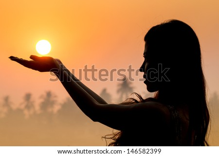 Portrait of young woman as silhouette and hand holding the sun - stock photo