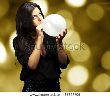 portrait of young woman blowing balloon against a abstract lights background